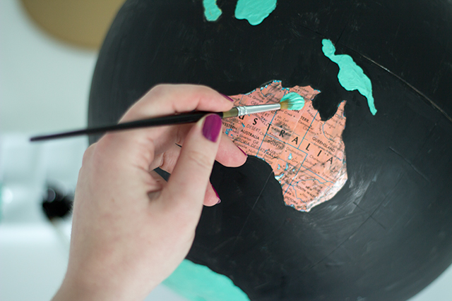 Painting the continents on a DIY anthropologie inspired wanderlust globe.