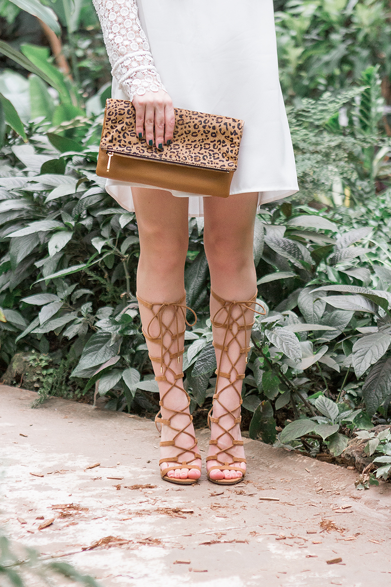 Feminine boho style. Coachella festival fashion inspiration with white off the shoulder dress, leopard print clutch and gladiator heels.