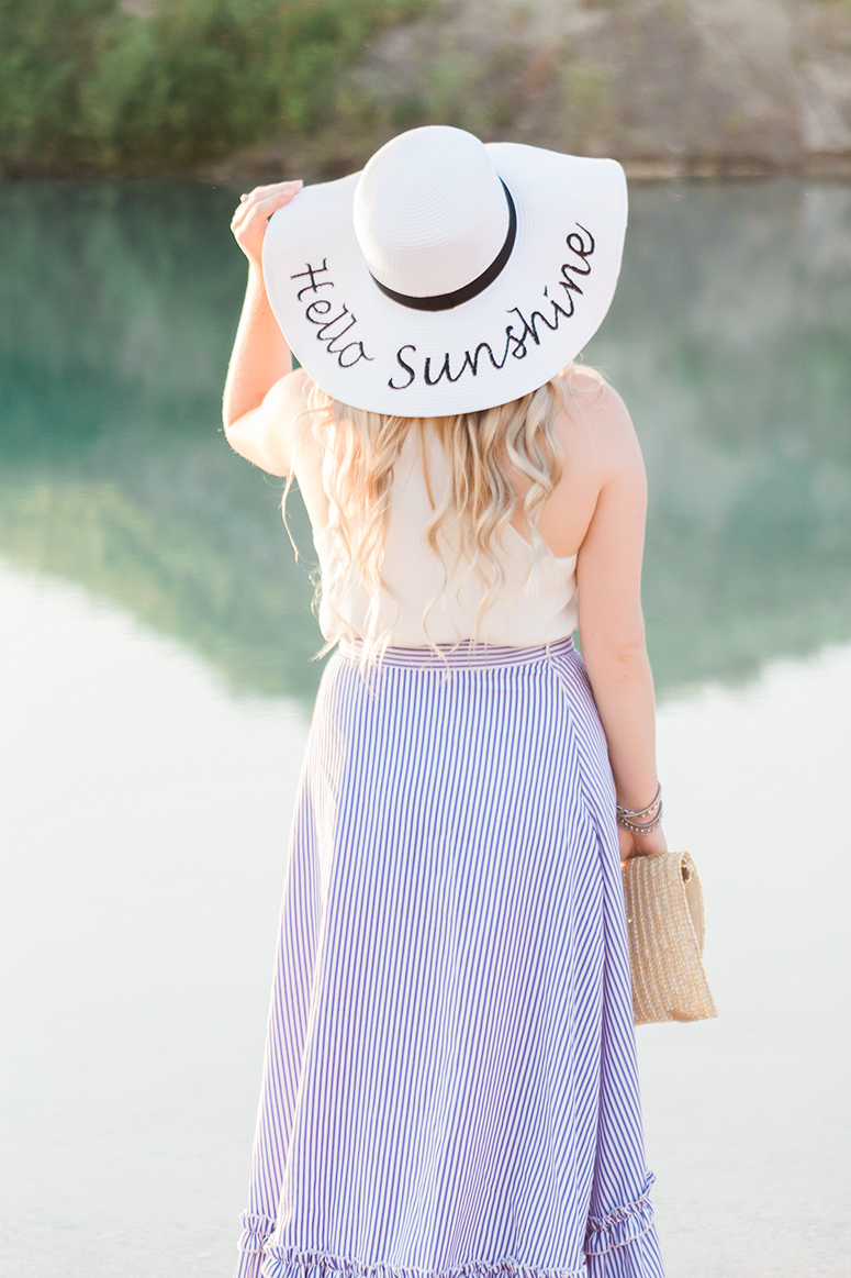 Romantic beach outfit. Striped ruffled skirt, straw clutch and a floppy hat.