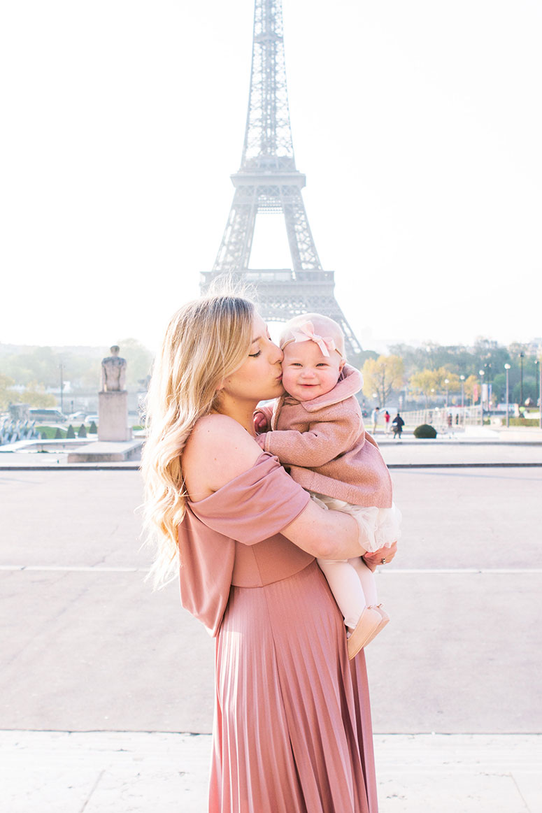 Traveling to Europe with a baby. Mom and baby girl in front of Eiffel tower.