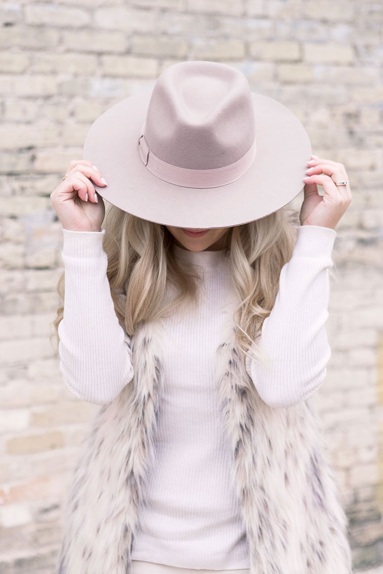 Monochromatic neutral outfit idea: How to wear tone on tone whites and taupes for an easy casual fall outfit. Fur vest with warm cougar winter boots and a fedora.
