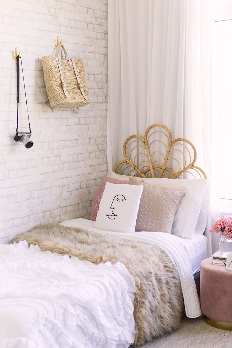 Rattan headboard with white ruffled blanket and diy face pillow.