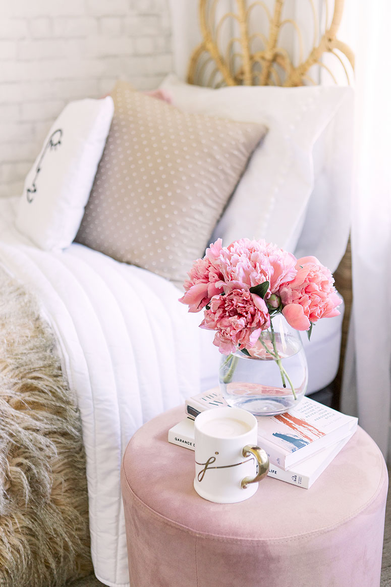 Coral pink peonies on a round pink velvet ottoman as end table.