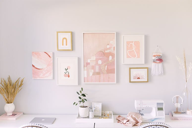 All pink gallery wall with relaxing bohemian style artwork.