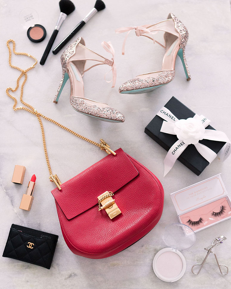 How to choose your first designer bag // Flatlay image with red Chloe Drew bag and sparkly accessories